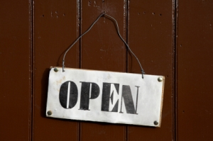 Open sign pinned onto a painted wooden door